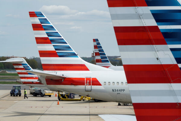 A member of a ground crew walks past American Airlines planes parked