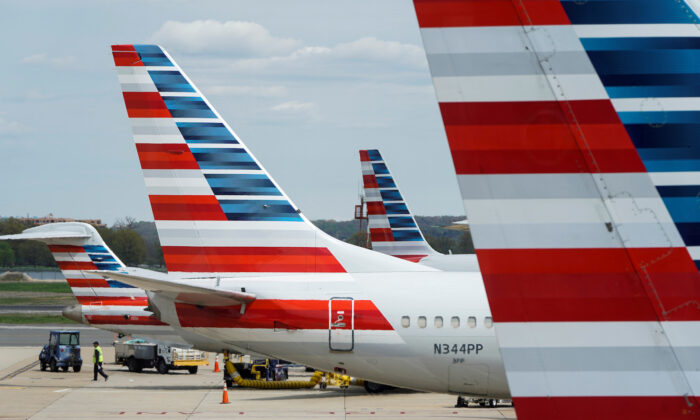 A member of a ground crew walks past American Airlines planes parked at the gate during the CCP virus outbreak at Ronald Reagan National Airport in  Washington, on April 5, 2020.(Joshua Roberts/Reuters)