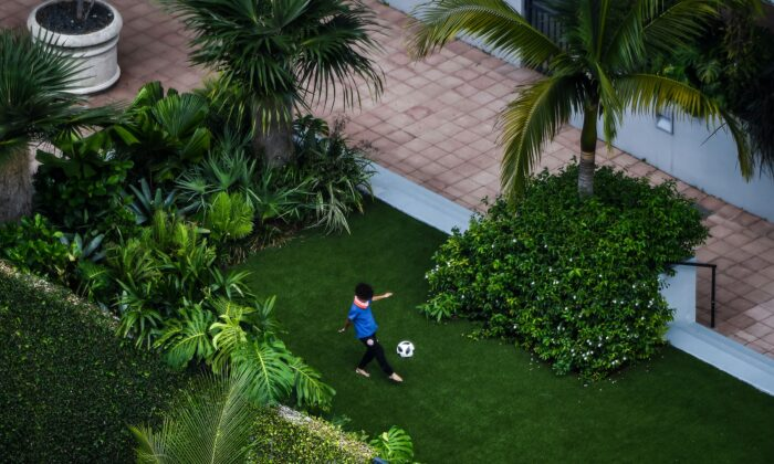 A boy plays football alone in a garden amid fears over the spread of the CCP virus in Miami, Florida, on April 6, 2020. (Chandan Khanna/AFP via Getty Images)