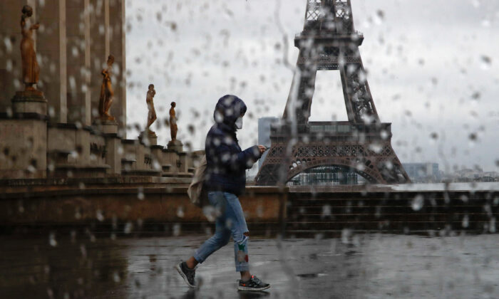 A woman with a protective face mask walks past the Eiffel tower in Paris on April 6, 2020. (Gonzalo Fuentes/Reuters)