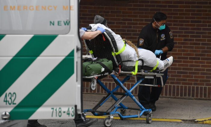 Paramedics push a gurney with a patient to the Brooklyn Hospital Center Emergency Room in New York City on March 31, 2020. (Angela Weiss/AFP via Getty Images)