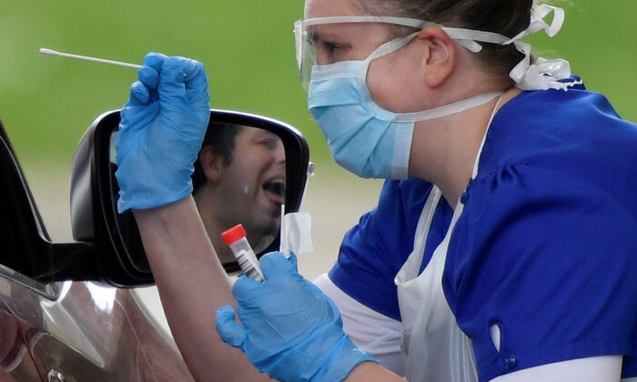 Medical staff testing people at a COVID-19 test centre in Chessington, UK, on April 2, 2020. (Toby Melville/Reuters)