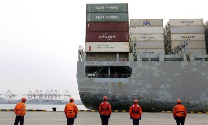Workers watch a container ship arrive at a port in Qingdao in east China's Shandong province , China, on Feb. 4, 2020. (Chinatopix via AP)