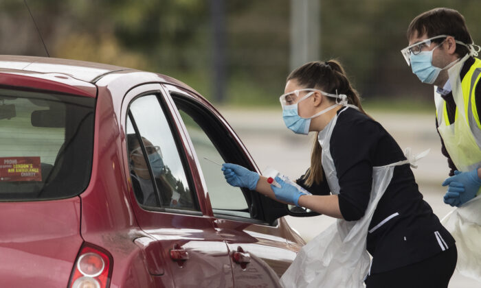 A nurse takes a swab at a Covid-19 drive-through testing station for NHS staff on March 30, 2020 in Chessington, United Kingdom. The Coronavirus (COVID-19) pandemic has spread to many countries across the world, claiming over 30,000 lives and infecting hundreds of thousands more. (Photo by Dan Kitwood/Getty Images)
