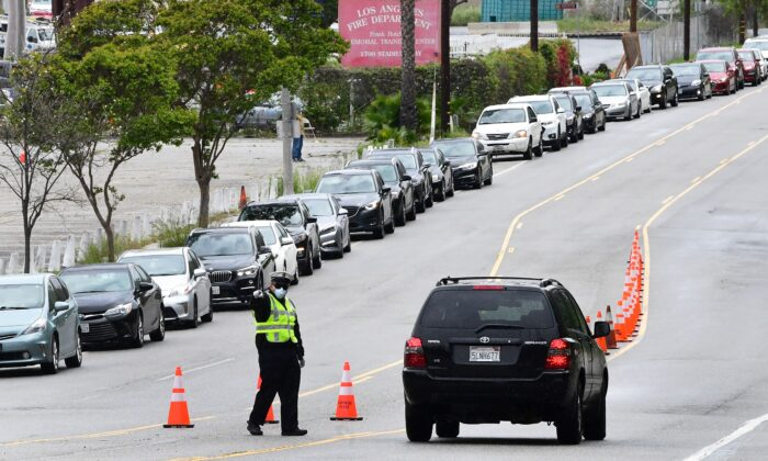 A police officer wearing a facemask offers directions to a motorist as people in a row of cars await Covid-19 testing near Dodger Stadium in Los Angeles, California on April 7, 2020, as Los Angeles County officials say the number of coronavirus cases has reached 6,910 with a death toll of 169. (Frederic J. Brown/AFP)