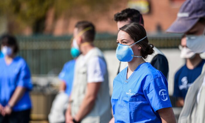 Volunteers looking on during the opening of a newly operative field hospital for coronavirus patients, financed by US evangelical Christian disaster relief NGO Samaritans Purse in Cremona, southeast of Milan on March 20, 2020. (Miguel Medina/AFP via Getty Images)