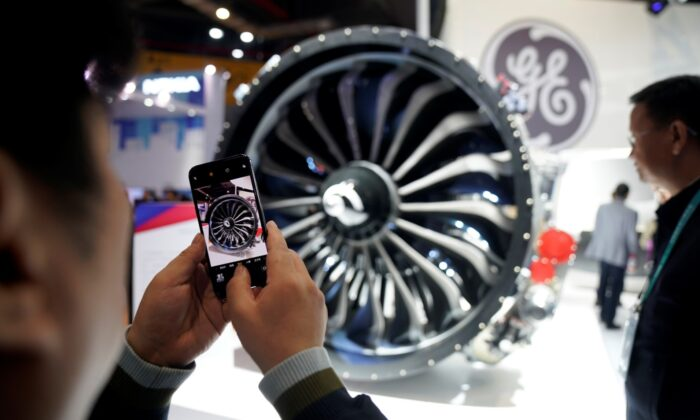 A man takes a picture of a General Electric engine during the China International Import Expo, at the National Exhibition and Convention Center in Shanghai, China, on Nov. 6, 2018. (Aly Song/File Photo/Reuters)