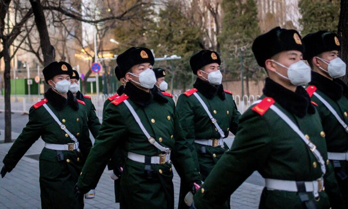Paramilitary police officers wearing face masks as they walk along a street in Beijing on March 1, 2020. (Nicolas Asfouri/AFP via Getty Images)