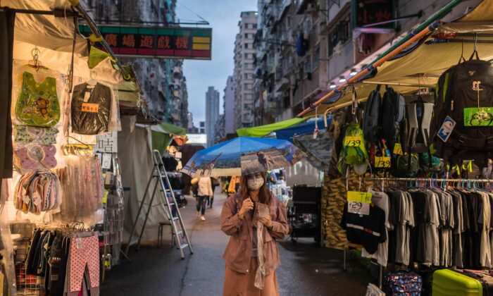 A woman wearing a face mask, amid concerns of the COVID-19 coronavirus, walks through a clothes market in Hong Kong, China, on April 5, 2020. (Dale De La Rey/AFP via Getty Images)