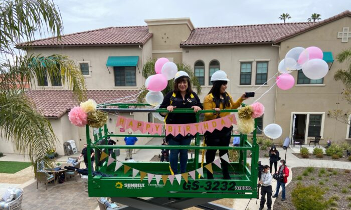 Lucy Cavazos (L) and her daughter ride a construction lift to see 91-year-old Margaret Jones at the assisted living facility The Kensington Redondo Beach on April 7, 2020. (Photo by Cristal Chavez/Courtesy of Lucy Cavazos)