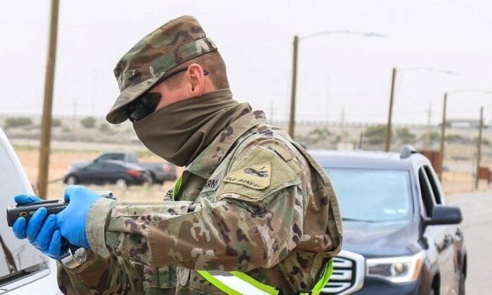 A soldier wears a makeshift face covering at a checkpoint in this handout image from April 6, 2020. (Department of Defense)