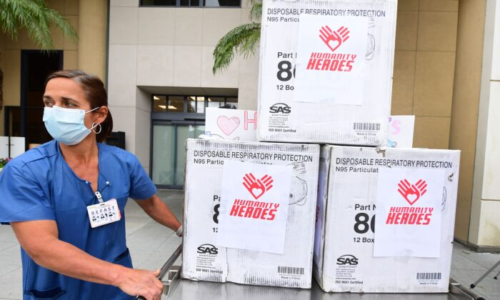 "A nurse wearing a protective mask pushes a cart of masks donated by U.S. businessperson Michael ""BigMike"" Straumietis, to the Providence Saint Joseph Medical Center in Burbank, Calif., on April 7, 2020,(Frederic J. Brown/AFP via Getty Images)"