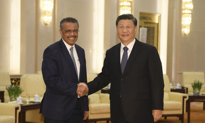 World Health Organization director general Tedros Adhanom (L) shakes hands with Chinese regime leader Xi jinping before a meeting at the Great Hall of the People in Beijing on Jan. 28, 2020. (Naohiko Hatta/AFP via Getty Images)
