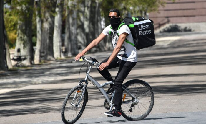 An Uber Eats delivery man with his face covered rides his bike in Montpellier, southern France on April 3, 2020. (Pascal Guyot/AFP via Getty Images)