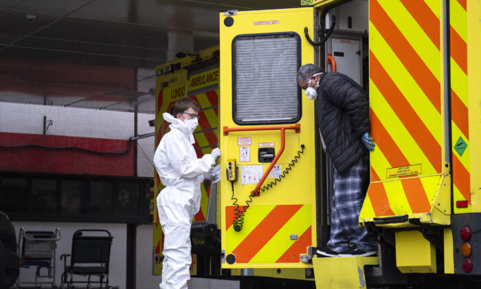 A man with an unknown condition is helped from an ambulance at the St Thomas' Hospital on March 30, 2020 in London, England. Hospitals across London are facing a surge in demand for critical care due to the coronavirus pandemic. (Justin Setterfield/Getty Images)