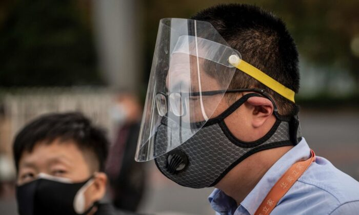 A man (R) wearing a facemask and a face shield commute on a street during rush hour in Beijing on April 7, 2020. (Nicolas Asfouri/AFP via Getty Images)