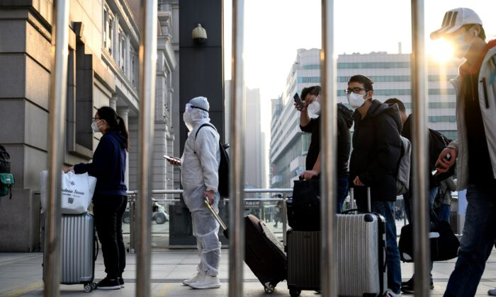 People wearing face masks arrive at Hankou Railway Station in Wuhan to take one of the first trains leaving the city in China's central Hubei Province early on April 8, 2020. (Noel Celis/AFP via Getty Images)