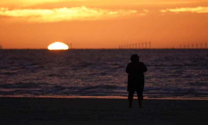 A solitary person walks on the beach at sunset in New Brighton, England, on March 19, 2020. (Christopher Furlong/Getty Images)