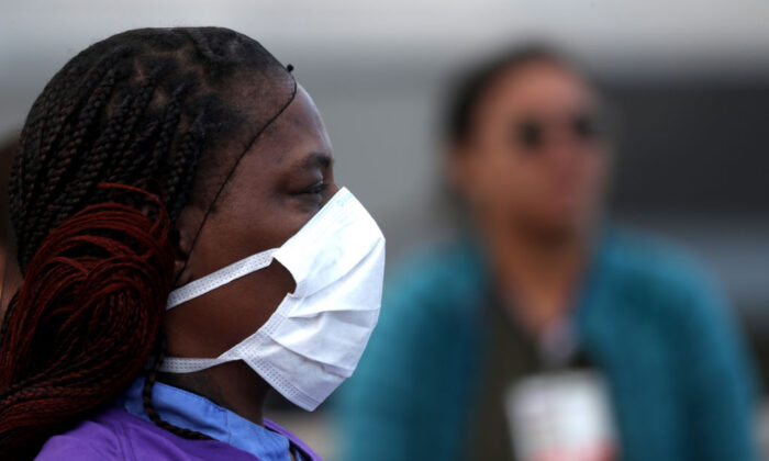 Alameda Health System nurses, doctors, and workers wear personal protective equipment (PPE) during a protest asking for better working conditions and PPE in front of Highland Hospital in Oakland, Calif., on March 26, 2020. (Justin Sullivan/Getty Images)