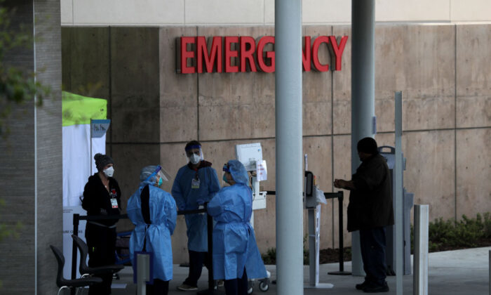 Health care professionals screen people entering the emergency room at Highland Hospital in Oakland, Calif., on March 26, 2020. (Justin Sullivan/Getty Images)