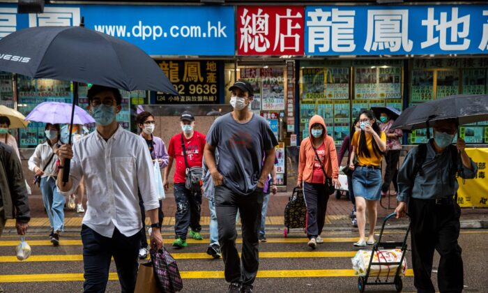 ImpactHK founder and CEO Jeff Rotmeyer (C) crosses a street after handing out supplies of face masks, hand sanitisers, food and drinks to the homeless and people in need in Hong Kong on March 28, 2020. (Isaac Lawrence/AFP via Getty Images)