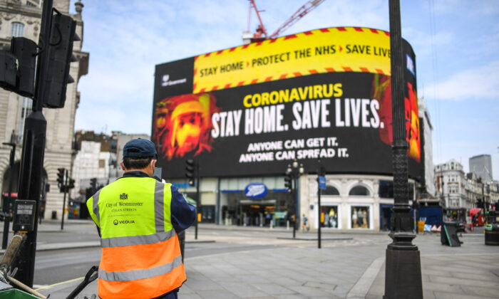 A street cleaner is seen in front of CCP virus messaging on Piccadilly Circus in London on April 8, 2020. (Peter Summers/Getty Images)