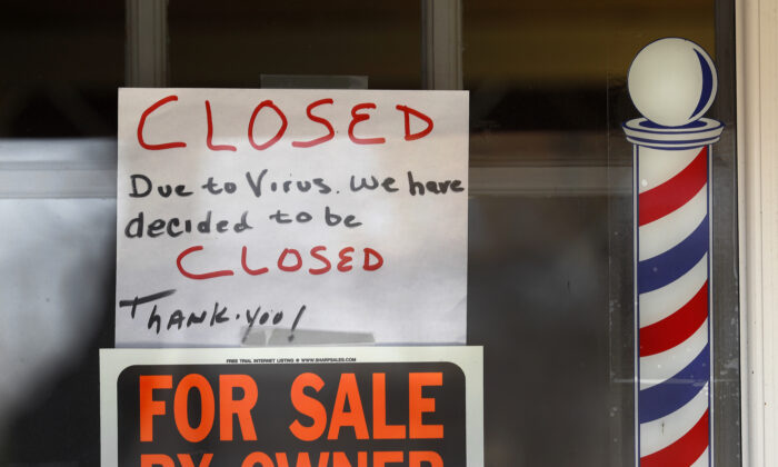 """For Sale By Owner"" and ""Closed Due to Virus"" signs are displayed in the window of Images On Mack in Grosse Pointe Woods, Mich., on April 2, 2020. (Paul Sancya/AP Photo)"