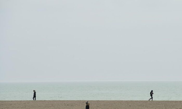 People practise physical distancing at Woodbine Beach in Toronto on March 26, 2020. (Nathan Denette/The Canadian Press)