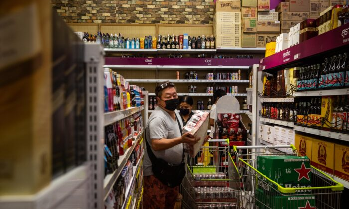 People wearing face masks purchase cases of beer at a grocery store in Bangkok, Thailand on April 9, 2020. (Lauren DeCicca/Getty Images)