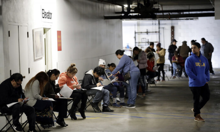 Unionized hospitality workers wait in line in a basement garage to apply for unemployment benefits at the Hospitality Training Academy in Los Angeles, Calif., on March 13, 2020. (Marcio Jose Sanchez/AP Photo)