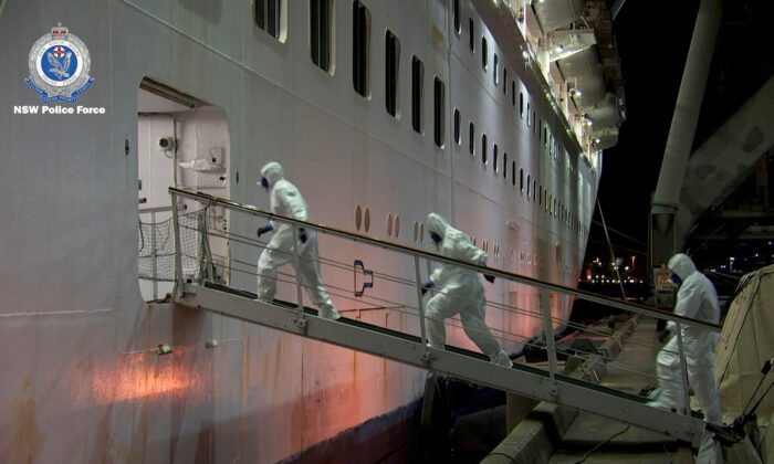 NSW Police personnel in personal protective equipment board the Ruby Princess during the Strike Force Bast raid of the cruise ship at Port Kembla, New South Wales, Australia on, April 8, 2020, in this still image from video. (NSW Police via Reuters)