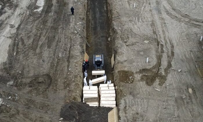 Workers wearing personal protective equipment bury bodies in a trench on Hart Island, on April 9, 2020. (John Minchillo/AP Photo)