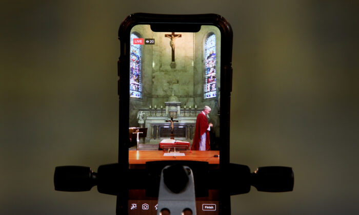 Bishop Richard Umbers is seen live-streaming via a mobile phone during 'The Celebration of the Passion of The Lord' service at St Paul of the Cross Church in Dulwich Hill, Australia, April 10, 2020. (Lisa Maree Williams/Getty Images)