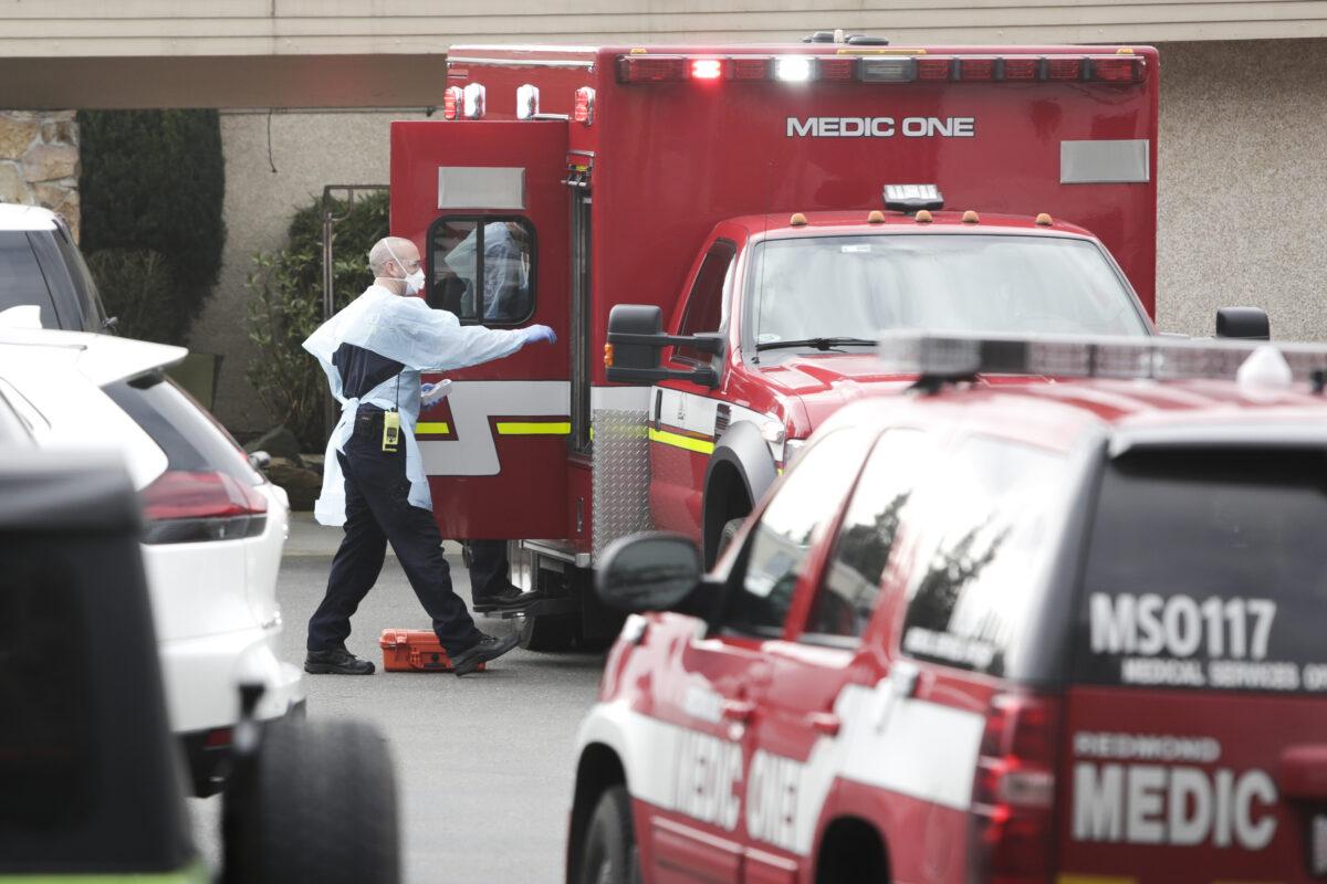 Ambulance staff prepare to transport a patient