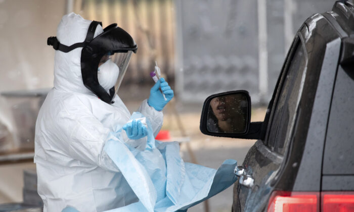 A nurse dressed in personal protective equipment prepares to give a COVID-19 swab test at a drive-thru testing station in Stamford, Connecticut, on March 23, 2020. (John Moore/Getty Images)