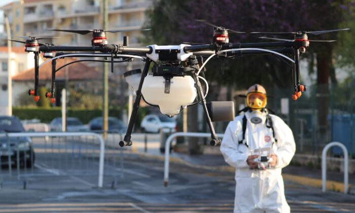 A technician flies a drone that will spray disinfectant along the streets of Cannes, France, on April 10, 2020. (Valery Hache /AFP via Getty Images)
