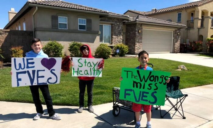 Elementary school students hold signs while watching a car parade organized by their teachers in French Valley, Calif. (Courtesy of Dawn Marie Wong)
