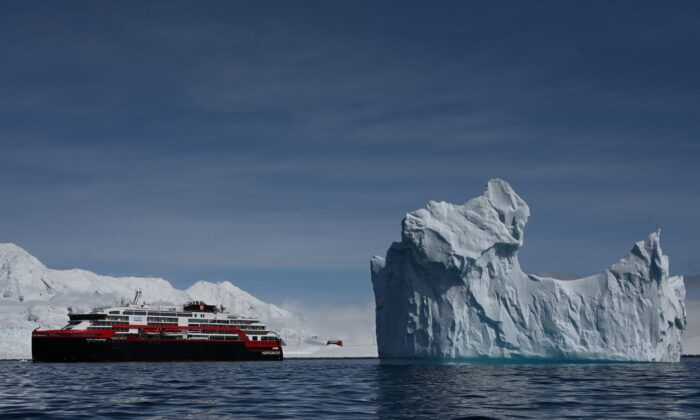 View of an iceberg and the Hurtigruten hybrid expedition cruise ship MS Roald Amundsen on Half Moon island, Antarctica on November 09, 2019. (by JOHAN ORDONEZ/Getty Images)