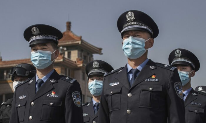 Chinese police officers wear protective masks as they observe three minutes of silence to mark the country's national day of mourning for COVID-19 at Beijing Railway Station in Beijing, China, on April 4, 2020. (Kevin Frayer/Getty Images)