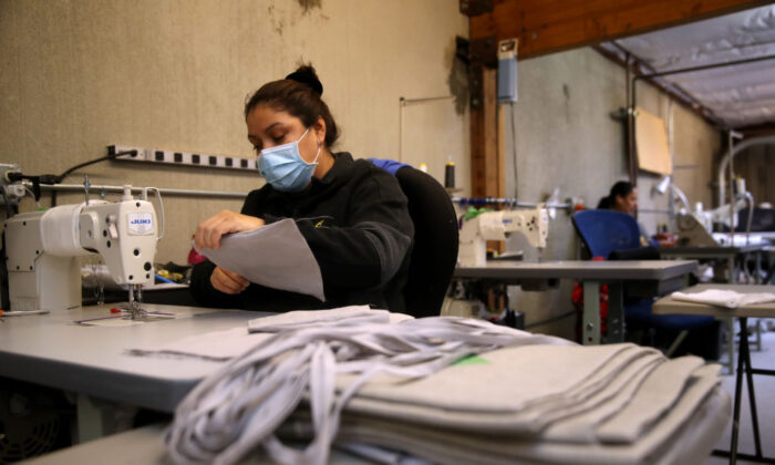 A worker at Rough Linen sews fabric masks in San Rafael, Calif., on April 6. Rough Linen, a maker of handcrafted linen bedding, has changed its production line and is now making fabric masks that are being donated to local hospitals and healthcare workers. (Photo by Justin Sullivan/Getty Images)
