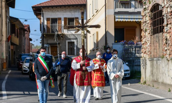 Parish priest of the Santa Maria Assunta church in Pontoglio, Don Giovanni Cominardi (C), is escorted by Pontoglio mayor Alessandro Seghezzi (L), during a Via Crucis procession (Way of the Cross) as part of Good Friday celebrations in Pontoglio, Italy, on April 10, 2020. (Miguel Medina /AFP via Getty Images)