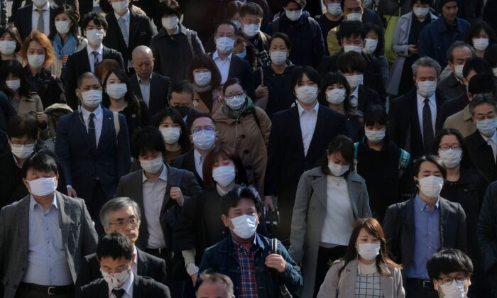 Face mask-clad commuters head to work through a street connecting from Shinjuku railway station in Tokyo, Japan, on April 9, 2020. (Kazuhiro NogiI/AFP via Getty Images)