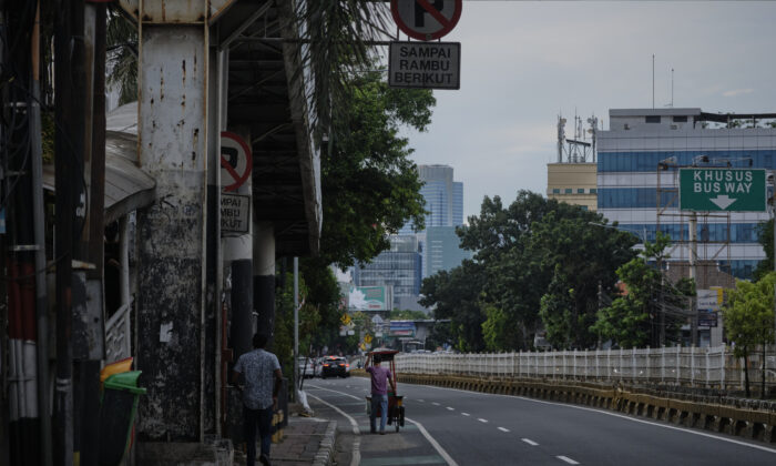 A stretches vendor pushes his cart along a road which would ordinarily be bumper to bumper traffic in Jakarta, Indonesia, on April 8, 2020. (Ed Wray/Getty Images)