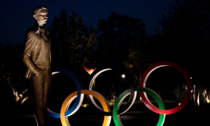 The statue of founder of the International Olympic Committee Pierre de Coubertin and the Olympic rings in Tokyo on April 7, 2020. (Behrouz Mehri /AFP via Getty Images)