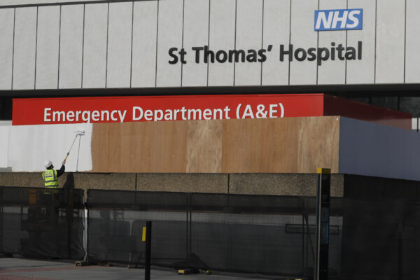 Worker paints fence to block the view of the ambulance entrance area outside St Thomas' Hospital in central London, where British Prime Minister Boris Johnson remains in intensive care.