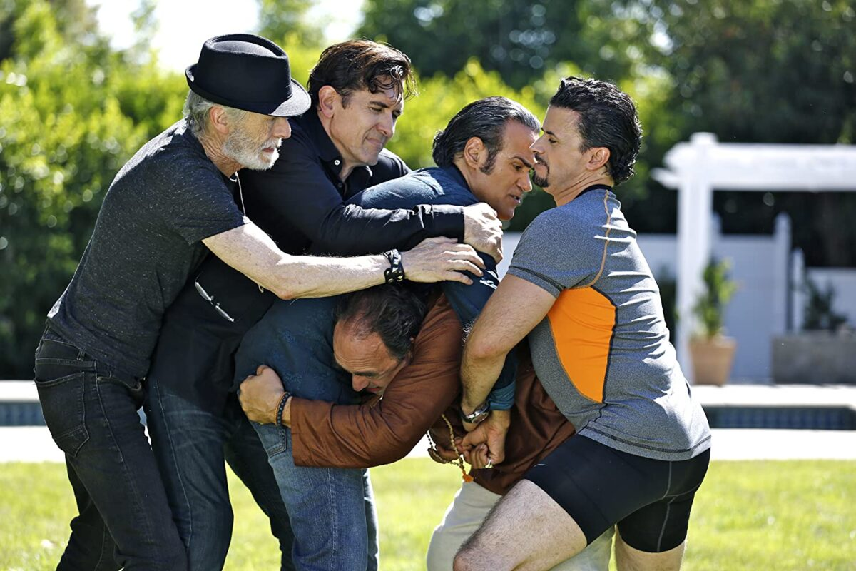 """five men wrestling on a lawn in """"Welcome to the Men's Group"""""""