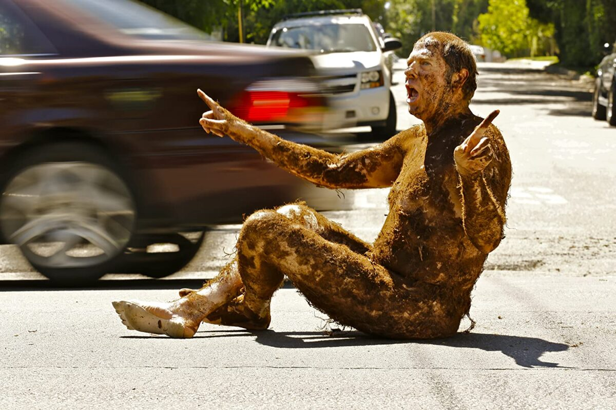 """Naked man covered with dirt sitting in street in """"Welcome to the Men's Group"""""""