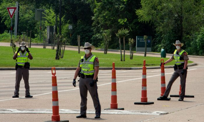 Texas State Troopers wait for drivers to arrive at a check point at the Texas Travel Information Center on the Louisiana-Texas border in Orange, Texas on April 7, 2020. (Mark Felix/AFP via Getty Images)