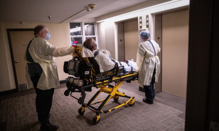 Medics wearing personal protection equipment, transport a patient showing COVID-19 symptoms from his apartment in Stamford, Connecticut on April 4, 2020. (John Moore/Getty Images)