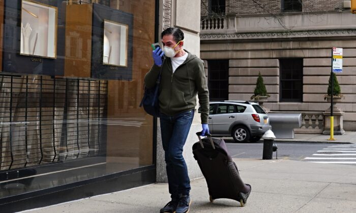 A man wearing a protective mask and gloves talks on a cell phone in a ziplock bag during the COVID-19 pandemic in New York City on April 8, 2020. (Cindy Ord/Getty Images)